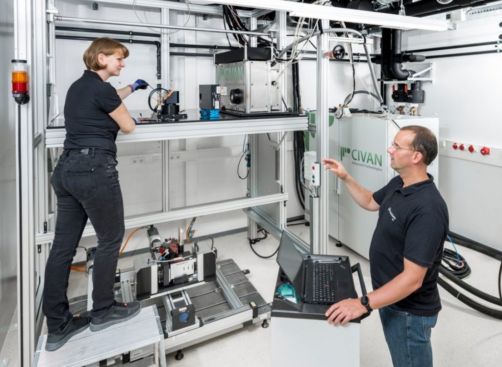 Two engineers installing the CIVAN 3D printer at Fraunhofer IWS.