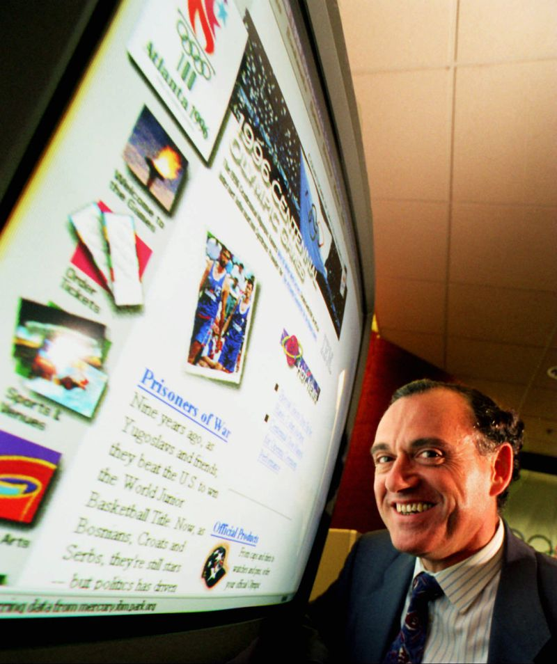 """Jose-Luis Iribarren poses in front of the ACOG website developed by IBM in 1996. """"We kept adding things along the way,"""" said Iribarren recently. """"I don't even know how did we manage to get to launch the website in time."""" (Joey Ivansco / AJC file)"""